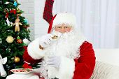 Santa Claus sitting on sofa with  milk and cookies near Christmas tree
