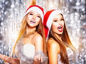 Christmas party girls. Beauty teen girls in santa hat singing and dancing over holiday blinking background. Disco. New year celebration