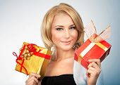 Portrait of pretty woman with two shiny gift boxes in hands over gray background, Christmas time holidays concept
