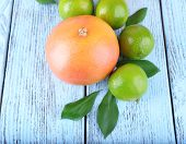 Ripe grapefruits and limes on wooden background