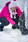 Young woman putting winter chains on car