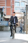 Young businessman riding bicycle on urban street