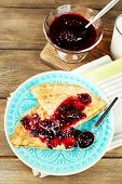 Plate of delicious pancakes with berry jam on plate on wooden background