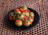 Green olives in oil with spices and rosemary on plate on braided table