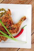 roast meat : roasted chicken legs garnished with green peas , peppers , and garlic on white plates over wooden table