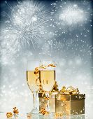 Glasses with champagne and gift box over sparkling holiday background