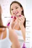 Reflection of smiling young girl putting mascara