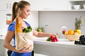 Woman  in kitchen holding a shopping bag full of fresh food