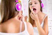 Teenager girl make up and  listening to music