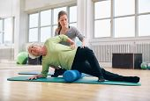 foto of therapist massage  - Female instructor helping senior woman using a foam roller for a myofascial release massage at gym - JPG