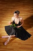 Ballerina in black costume with rose