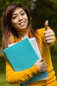 Portrait of female college student with books gesturing thumbs up in the park