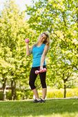 Fit blonde lifting dumbbells in the park on a sunny day