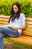 Smiling brunette sitting on bench reading in the park