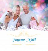 happy couple with shopping bags against Christmas greeting card