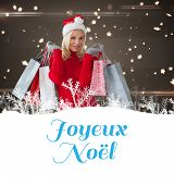 happy festive blonde with shopping bags against joyeux noel