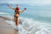 Santa Girl Making Wish On The Beach In Tropics