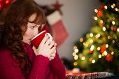 Beautiful redhead drinking hot drink at christmas at home in the living room