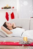 Relaxed brunette lying on the couch at christmas against snow falling