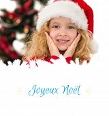 Festive little girl smiling at camera against Christmas greeting card