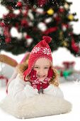 Festive little girl in hat and scarf against snow falling