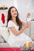 Happy brunette holding heart for decoration against snow falling