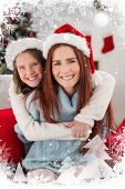 Festive mother and daughter on the couch against christmas theme frame in silver