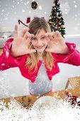 Festive little girl making christmas cookies against snow falling