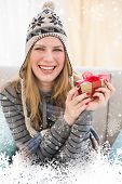 Happy blonde in winter hat sitting on couch showing a gift against snow falling