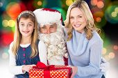 Mother and daughter with santa claus against colourful glowing dots on black
