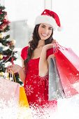 Smiling brunette in red dress holding shopping bags against snow falling