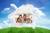 Happy family lying in bed and smiling at the camera against green hill under blue sky