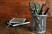 Metal holder with pens, pencil and scissor near the notebooks on rustic wooden background