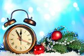 Alarm clock with Christmas decorations on bright background