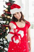 Festive brunette in red dress holding gift at christmas against snow falling