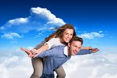 Smiling young man carrying woman against bright blue sky with clouds