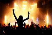 Concert, disco party. Woman silhouette with hands up in foreground and people having fun in night club