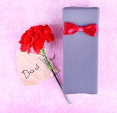 Happy Father's Day with gift box, red carnation and piece of paper on texture background
