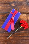 Present box with red carnation on wooden background