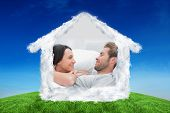Cheerful couple awaking and looking at each other against green hill under blue sky
