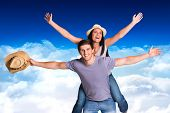 Man giving his pretty girlfriend a piggy back against bright blue sky over clouds