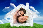 Woman looking at her friend while lying head to shoulder with him against green field under blue sky