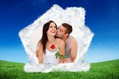 Lovers sitting on bed with a rose against green field under blue sky