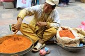 KATHMANDU, NEPAL - APRIL 2014 :  A street vendor selling ground turmeric, cumin in a metal Kharpan in Kathmandu, Nepal on 12 April 2014. Turmeric powder is the main herbs that is used in Nepali dishes