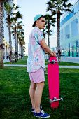 Young hipster man standing on the grass holding his longboard stylish teenager man stand in park