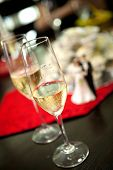 Two glasses of champagne on table with bride and groom plastic figure in background showing a wedding event.