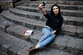 Smiling student girl making a self portrait with smart phone sitting on steps