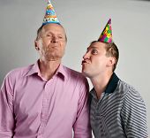 birthday men with party hats grimacing