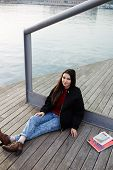 Charming tourist girl sitting on wooden pier enjoying beautiful view of Barcelona port