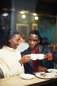 Happy stylish friends having coffee together laughing young couple in cafe having a great time